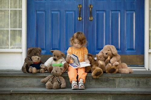 Garotinha lendo junto com seus ursinhos - Corbis