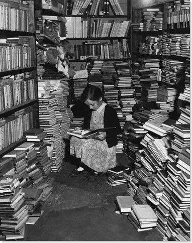 A little girl engrossed in a book in a corner of Foyles' bookshop, London. © Hulton-Deutsch Collection/CORBIS